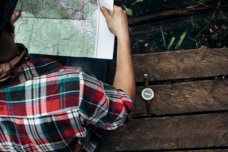 stylish hipster traveler exploring map at sunny forest and lake in the mountains; Shutterstock ID 366906749